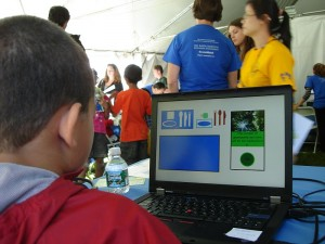 Visitors to Lamont Doherty Open House 2010 play with an interactive environmental decision game at the CRED table.
